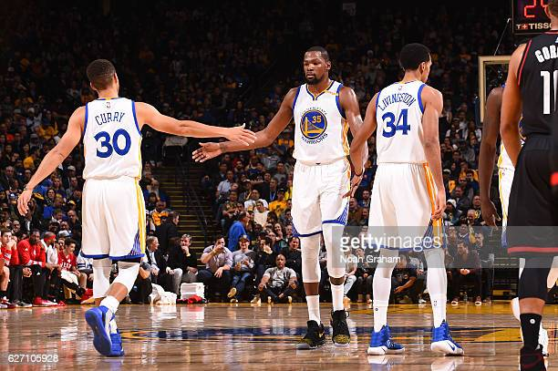 Kevin Durant of the Golden State Warriors celebrates with Stephen Curry and Shaun Livingston during a game against the Houston Rockets on December 1...
