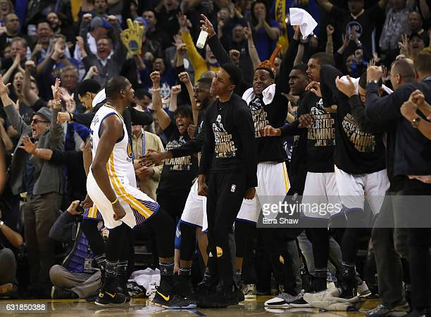 Kevin Durant of the Golden State Warriors celebrates with the bench after he made a shot against the Cleveland Cavaliers at ORACLE Arena on January...
