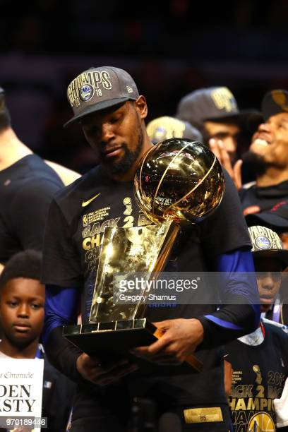 Kevin Durant of the Golden State Warriors celebrates with the Larry O'Brien Trophy after defeating the Cleveland Cavaliers during Game Four of the...