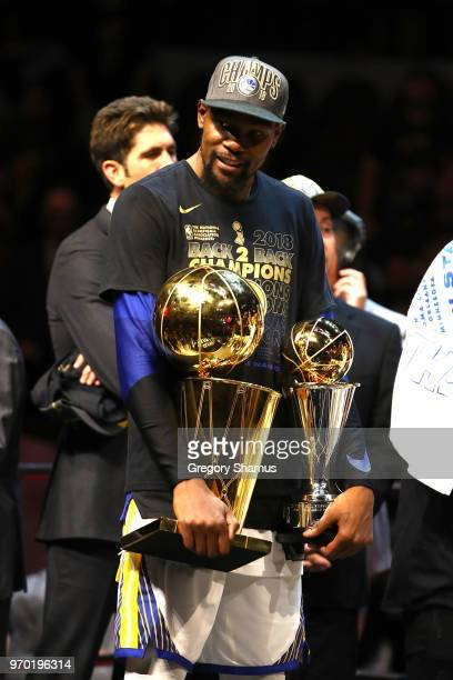 Kevin Durant of the Golden State Warriors celebrates with the Larry O'Brien Trophy and MVP Trophy after defeating the Cleveland Cavaliers during Game...