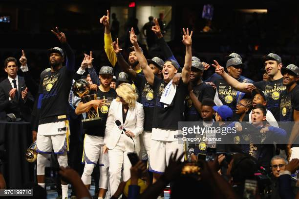 Kevin Durant of the Golden State Warriors celebrates with the MVP trophy as Stephen Curry celebrates with the Larry O'Brien Trophy after defeating...