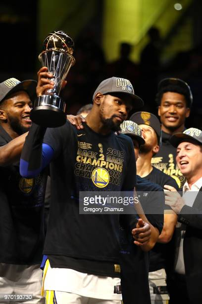 Kevin Durant of the Golden State Warriors celebrates with the NBA Finals MVP trophy after defeating the Cleveland Cavaliers during Game Four of the...