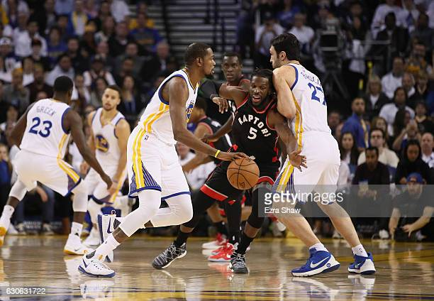 Kevin Durant of the Golden State Warriors dribbles around a pick set by Zaza Pachulia while guarded by DeMarre Carroll of the Toronto Raptors at...