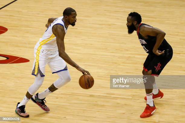 Kevin Durant of the Golden State Warriors dribbles the ball defended by James Harden of the Houston Rockets in the first half during Game Two of the...