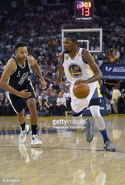 Kevin Durant of the Golden State Warriors dribbles the ball past Kyle Anderson of the San Antonio Spurs during the first quarter in an NBA basketball...