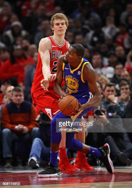 Kevin Durant of the Golden State Warriors drives against Lauri Markkanen of the Chicago Bulls at the United Center on January 17 2018 in Chicago...
