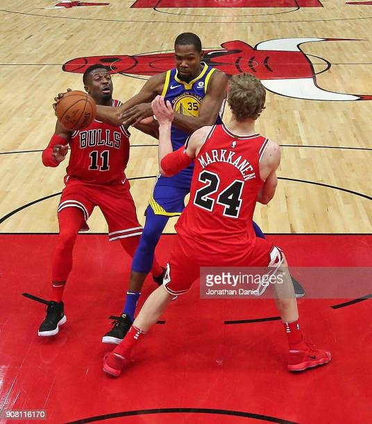 Kevin Durant of the Golden State Warriors drives between David Nwaba and Lauri Markkanen of the Chicago Bulls at the United Center on January 17 2018...