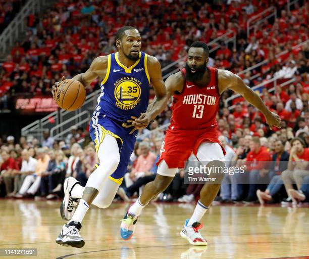 Kevin Durant of the Golden State Warriors drives to the basket defended by James Harden of the Houston Rockets in the fourth quarter during Game...