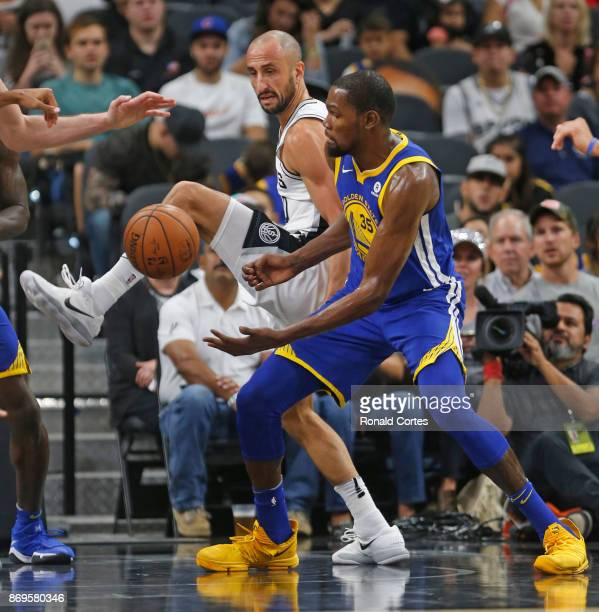 Kevin Durant of the Golden State Warriors fights for loose ball with Manu Ginobili of the San Antonio Spurs at ATT Center on November 2 2017 in San...