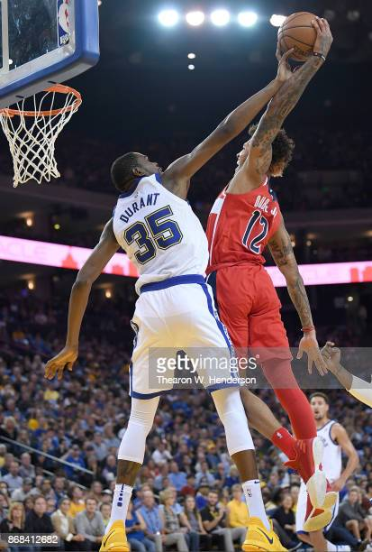 Kevin Durant of the Golden State Warriors gets called for a foul while blocking the shot of Kelly Oubre Jr #12 of the Washington Wizards during their...