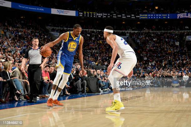 Kevin Durant of the Golden State Warriors handles the ball against Ben Simmons of the Philadelphia 76ers on March 2 2019 at the Wells Fargo Center in...