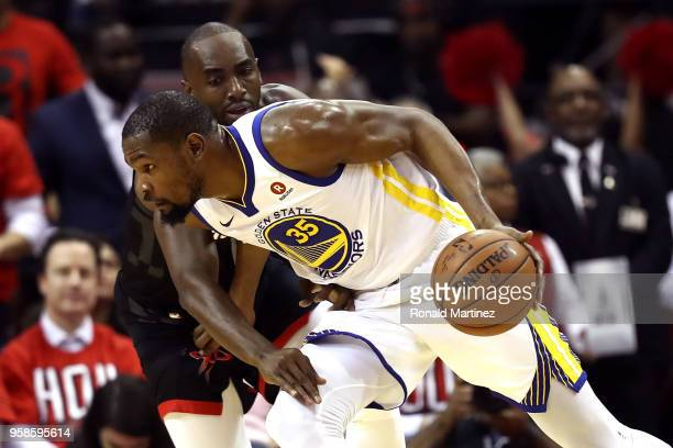 Kevin Durant of the Golden State Warriors handles the ball against Luc Mbah a Moute of the Houston Rockets in the first half in Game One of the...