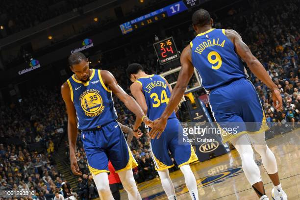 Kevin Durant of the Golden State Warriors hi fives Andre Iguodala of the Golden State Warriors on November 13 2018 at ORACLE Arena in Oakland...
