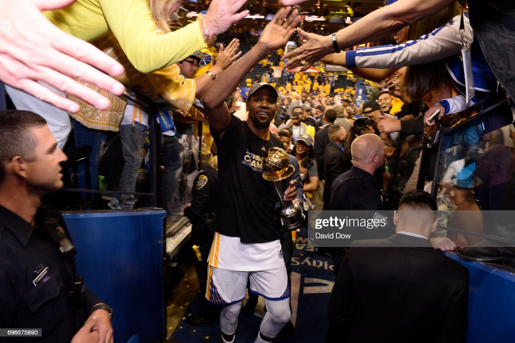 Kevin Durant #35 of the Golden State Warriors high fives fans as he walks off the court with the Bill Russell Finals MVP Trophy after winning Game Five of the 2017 NBA Finals against the Cleveland Cavaliers on June 12, 2017 at ORACLE Arena in Oakland, California.