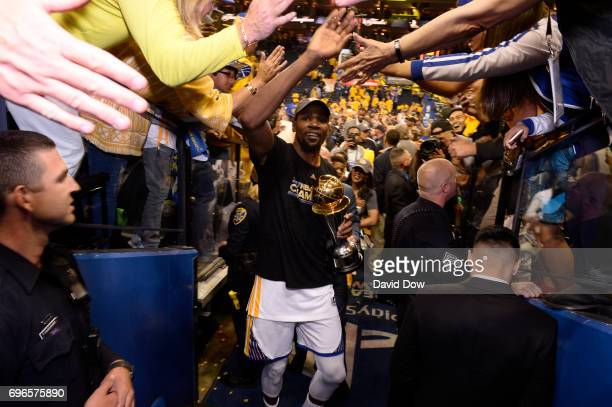 Kevin Durant of the Golden State Warriors high fives fans as he walks off the court with the Bill Russell Finals MVP Trophy after winning Game Five...