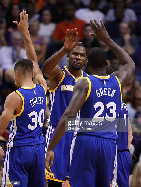 Kevin Durant of the Golden State Warriors high fives Stephen Curry and Draymond Green after scoring against the Phoenix Suns during the second half...