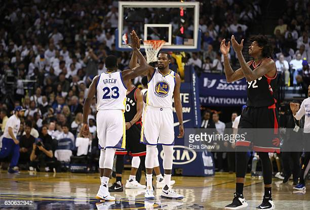 Kevin Durant of the Golden State Warriors highfives Draymond Green as Lucas Nogueira of the Toronto Raptors reacts at the end of the first quarter at...