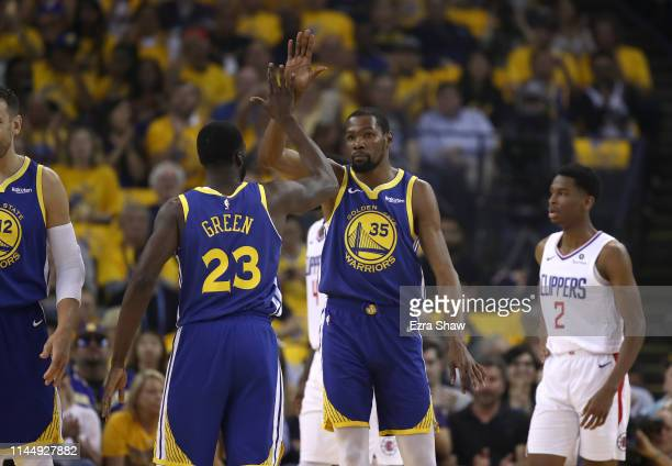 Kevin Durant of the Golden State Warriors highfives Draymond Green of the Golden State Warriors during their game against the LA Clippers during Game...