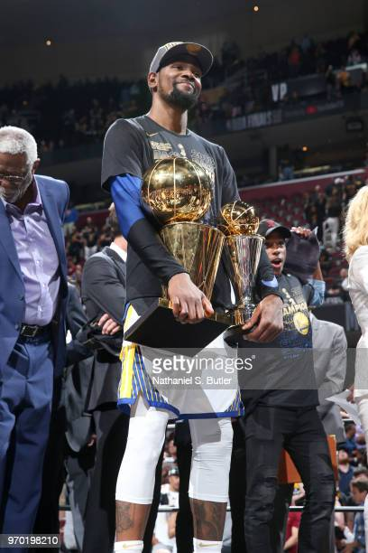 Kevin Durant of the Golden State Warriors holds the Larry O'Brien Championship Trophy and the Bill Russell NBA Finals MVP Trophy after Game Four of...
