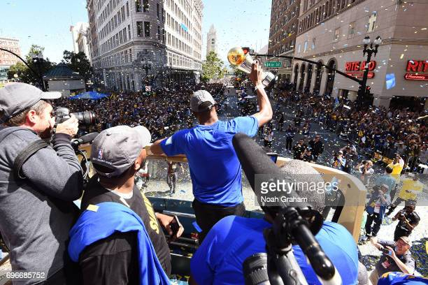 Kevin Durant of the Golden State Warriors holds up the Bill Russell Finals MVP Trophy during the Victory Parade and Rally on June 15 2017 in Oakland...