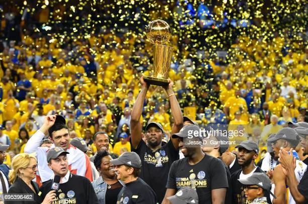 Kevin Durant of the Golden State Warriors holds up the Larry O'Brien trophy after winning the NBA Championship by defeating the Cleveland Cavaliers...
