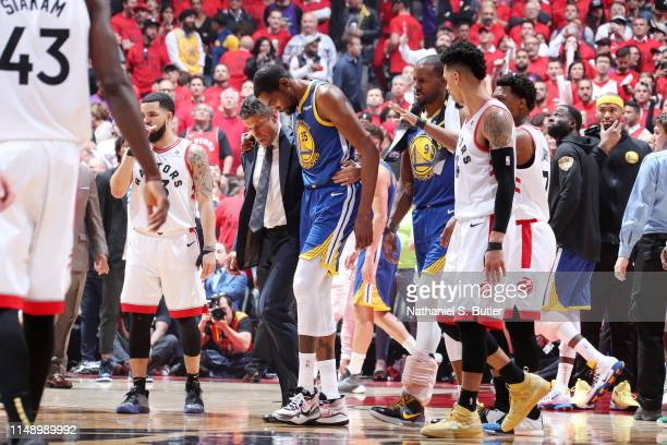 Kevin Durant of the Golden State Warriors is assisted off court after injuring his leg against the Toronto Raptors during Game Five of the NBA Finals...