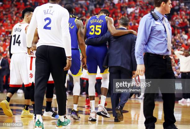 Kevin Durant of the Golden State Warriors is assisted off the court after sustaining an injury in the first half against the Toronto Raptors during...
