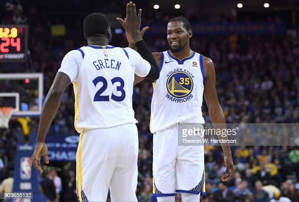 Kevin Durant of the Golden State Warriors is congratulated by Draymond Green for scoring his 25th point of the game during the first half of their...