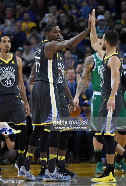 Kevin Durant of the Golden State Warriors is congratulated by Stephen Curry after Durant scored and was fouled in the act of shooting by Marcus...