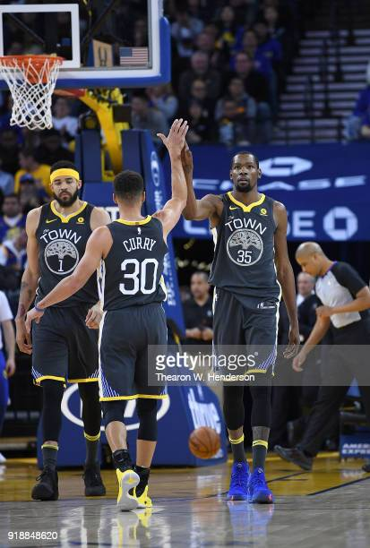 Kevin Durant of the Golden State Warriors is congratulated by Stephen Curry after Durant scored and got fouled against the Phoenix Suns during an NBA...
