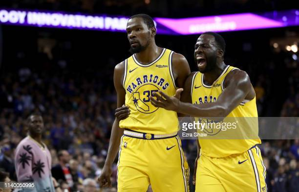 Kevin Durant of the Golden State Warriors is escorted off the court by Draymond Green after Durant was ejected from the game for complaining about a...