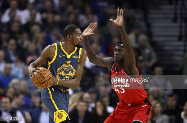Kevin Durant of the Golden State Warriors is guarded by Pascal Siakam of the Toronto Raptors at ORACLE Arena on December 12 2018 in Oakland...