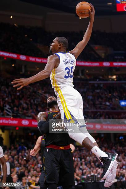 Kevin Durant of the Golden State Warriors leaps over LeBron James of the Cleveland Cavaliers for the dunk during the game at Quicken Loans Arena on...