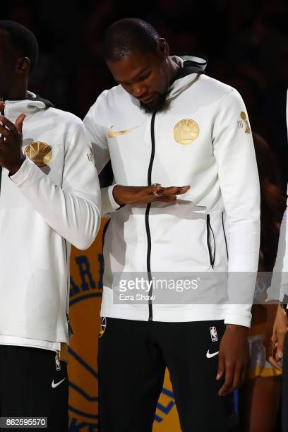 Kevin Durant of the Golden State Warriors looks at his2017 NBA Championship ring prior to their NBA game against the Houston Rockets at ORACLE Arena...