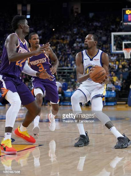 Kevin Durant of the Golden State Warriors looks to shoot over Deandre Ayton and Trevor Ariza of the Phoenix Suns during an NBA basketball game at...