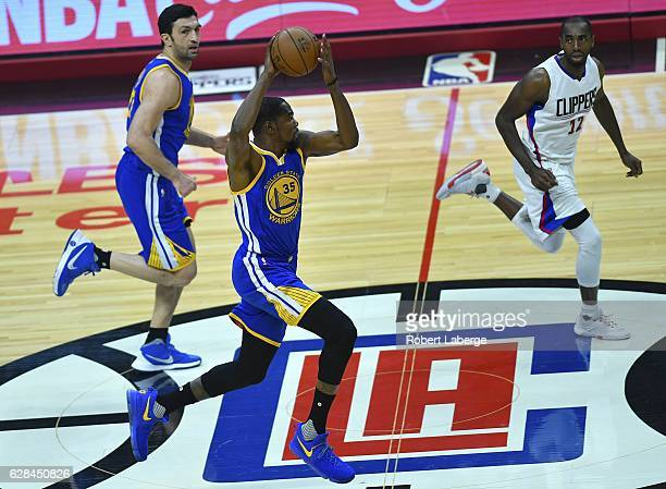 Kevin Durant of the Golden State Warriors plays against against Luc Mbah a Moute of the Los Angeles Clippers as Zaza Pachulia of the Warriors looks...