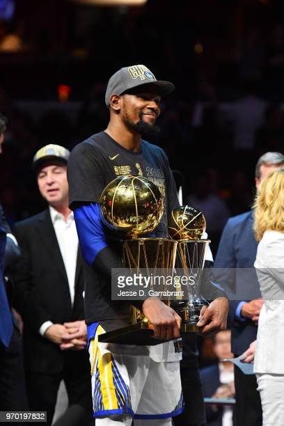 Kevin Durant of the Golden State Warriors poses for a photo with the Larry O'Brien Championship trophy and the Bill Russell Finals MVP trophy after...