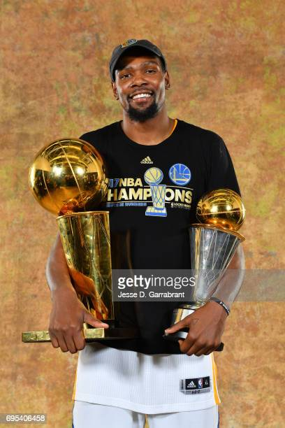 Kevin Durant of the Golden State Warriors poses for a portrait with the Larry O'Brien Trophy after defeating the Cleveland Cavaliers in Game Five of...