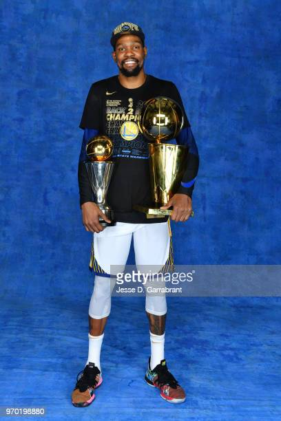 Kevin Durant of the Golden State Warriors poses for a portrait with the Larry O'Brien Championship trophy and the Bill Russell Finals MVP trophy...