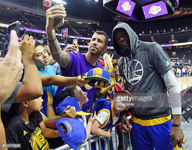 Kevin Durant of the Golden State Warriors poses for selfies with fans before a preseason game against the Los Angeles Lakers at TMobile Arena on...