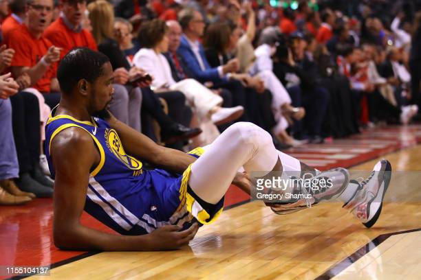 Kevin Durant of the Golden State Warriors reacts after sustaining an injury during the second quarter against the Toronto Raptors during Game Five of...