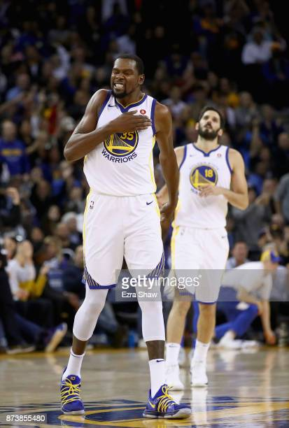Kevin Durant of the Golden State Warriors reacts after teammate Shaun Livingston dunked the ball against the Orlando Magic at ORACLE Arena on...