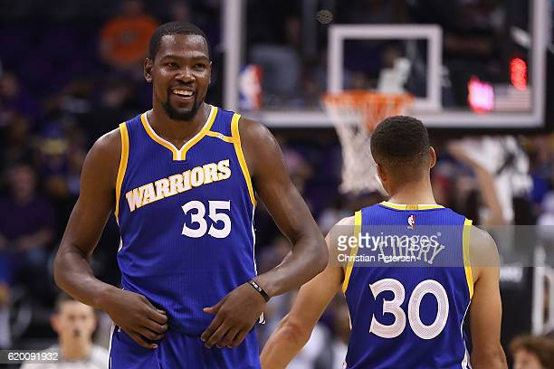 Kevin Durant of the Golden State Warriors reacts alongside Stephen Curry during the NBA game against the Phoenix Suns at Talking Stick Resort Arena...