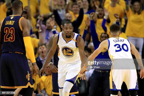 Kevin Durant of the Golden State Warriors reacts with Stephen Curry after a play against the Cleveland Cavaliers in Game 1 of the 2017 NBA Finals at...
