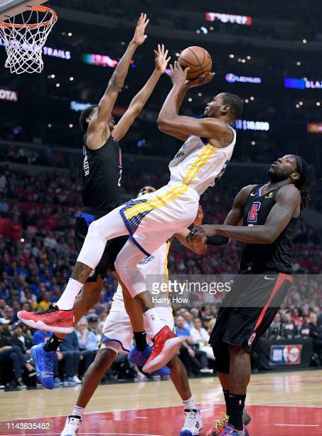 Kevin Durant of the Golden State Warriors scores as he is fouled between Shai GilgeousAlexander and Montrezl Harrell of the LA Clippers during Game...