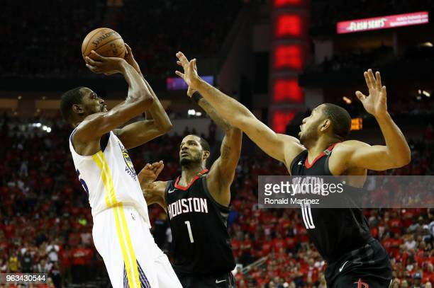 Kevin Durant of the Golden State Warriors shoots against Trevor Ariza and Eric Gordon of the Houston Rockets in the third quarter of Game Seven of...