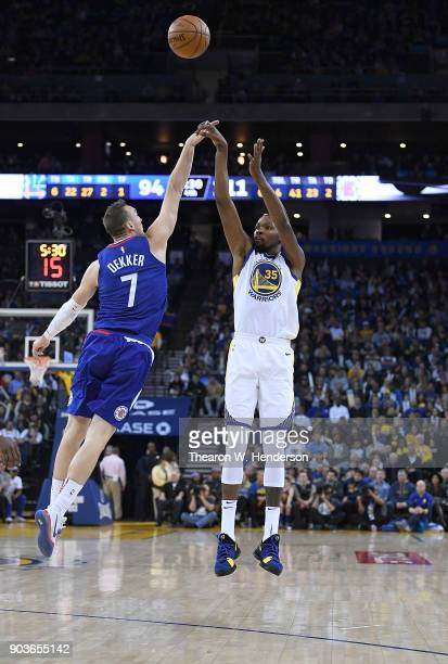 Kevin Durant of the Golden State Warriors shoots and scores a threepoint shot over Sam Dekker of the LA Clippers during the second half of their NBA...