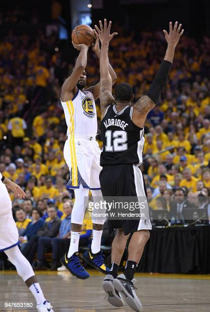 Kevin Durant of the Golden State Warriors shoots over LaMarcus Aldridge of the San Antonio Spurs in the first quarter during Game One of the first...