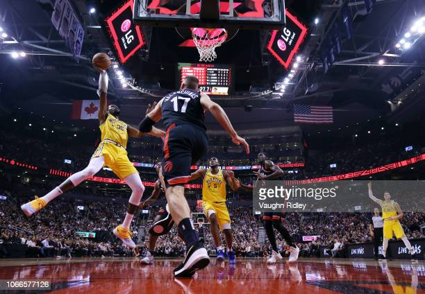 Kevin Durant of the Golden State Warriors shoots the ball as Jonas Valanciunas of the Toronto Raptors defends during the first half of an NBA game at...