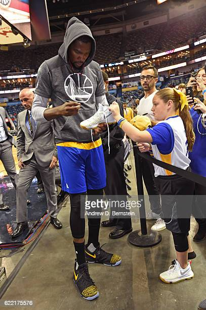 Kevin Durant of the Golden State Warriors signs an autograph for a fan prior to a game against the New Orleans Pelicans at Smoothie King Center on...